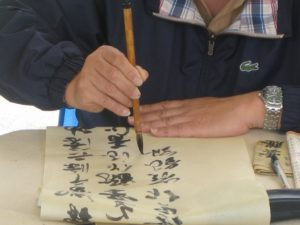 Maître Sun Fa de l'Académie Tian Long illustre la tenue du pinceau dans la calligraphie chinoise